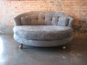 oversized living room chair large round chaise lounge with tufted back and wooden leg with wheel placed on concrete floor combined brick wall x